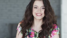 Attraktiv flicka med ett charmigt leende som poserar på kameran Stående av en ung brunett långsam rörelse arkivfilmer