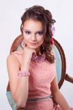 Attraktiv flicka med prydnader i konstsoutachen med lilor M Royaltyfri Foto