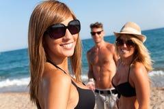 Attraktiv flicka med vänner på strand. Fotografering för Bildbyråer