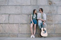 Attraktiv flicka och man med gitarren med gitarren som ser de på soligt arkivbild