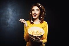 Attraktiv flicka som äter hållande ögonen på TV-program för smakligt salt sött popcorn arkivfoto