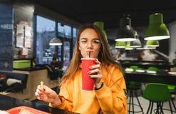 Attraktiv flicka som dricker en drink från en röd pappers- kopp arkivbild