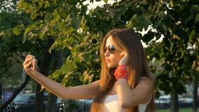 Attraktiv flicka som gör att le för selfie lager videofilmer