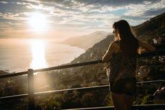 Attraktiv flicka som håller ögonen på en härlig solnedgång fotografering för bildbyråer