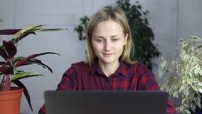 Attraktiv flicka som hemma arbetar på en bärbar dator lager videofilmer