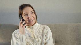 Attraktiv flicka som hemma sitter på en soffa och talar på hennes telefon royaltyfria bilder