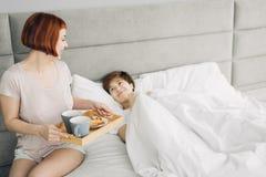 Attraktiv flicka som kommer med frukosten till hennes syster som ligger på sängen arkivfoton