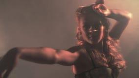 Attraktiv flicka som kraftigt dansar när ljuset lager videofilmer