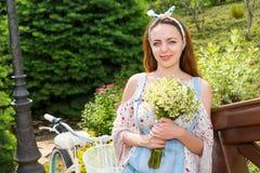 Attraktiv flicka som ler med blommor som står nära cykeln Arkivbilder