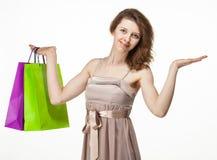 Attraktiv flicka som rymmer pappers- påsar för mångfärgad shopping arkivfoton