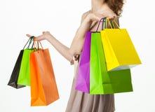 Attraktiv flicka som rymmer pappers- påsar för mångfärgad shopping royaltyfria bilder