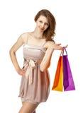 Attraktiv flicka som rymmer pappers- påsar för mångfärgad shopping royaltyfri bild