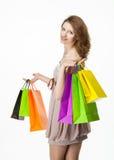 Attraktiv flicka som rymmer pappers- påsar för mångfärgad shopping arkivbilder