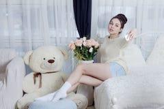 Attraktiv flicka som tar selfie med blommor på sängen i rummet Royaltyfri Foto