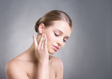 Attraktiv flicka som trycker på hennes släta hud över kinder på grå bakgrund Royaltyfri Fotografi