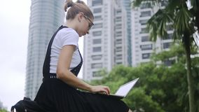 Attraktiv flicka som utomhus arbetar på bärbara datorn stock video
