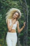 Attraktiv flickablondin med långt hår, på en grön bakgrund Royaltyfria Bilder