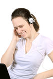attraktiv flickahörlurar med mikrofonbärbar dator Arkivbild