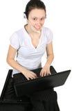 attraktiv flickahörlurar med mikrofonbärbar dator Arkivfoton