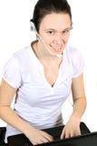 attraktiv flickahörlurar med mikrofonbärbar dator Arkivfoto