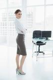 Attraktiv fridsam affärskvinna som poserar att stå i hennes kontor arkivbilder