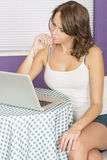 Attraktiv fundersam eftertänksam ung kvinna som använder bärbar datordatoren Arkivbild