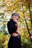 Attraktiv fundersam kvinna i en höstträdgård fotografering för bildbyråer