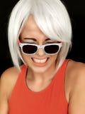 Attraktiv generad bärande solglasögon för ung kvinna Royaltyfria Foton