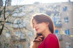 Attraktiv gladlynt flicka med gulligt sunt leende och sinnliga kanter som tycker om v?ren i staden under solig dag fotografering för bildbyråer