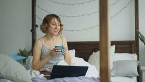 Attraktiv gladlynt kvinna som har online-video pratstund med vänner som använder bärbar datorkameran, medan sitta på säng hemma lager videofilmer