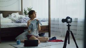 Attraktiv gladlynt kvinna som hemma sitter nära den videopd bloggen för sänginspelning om kläder för barn` s med dslrkameran lager videofilmer