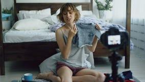 Attraktiv gladlynt kvinna som hemma sitter nära den videopd bloggen för sänginspelning om mode för barn` s med dslrkameran stock video