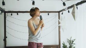 Attraktiv gladlynt kvinnadans på säng och sjunga med hårkammen som mikrofonen hemma arkivfilmer