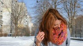 Attraktiv gladlynt le flicka i varmt lag och färgrika stack halsduken som poserar se kameran utomhus under stock video