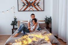 Attraktiv gladlynt man och kvinna på krama för säng Parkel arkivbild