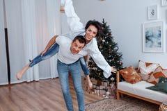 Attraktiv gladlynt man och kvinna som har gyckel nära julträd Helgdagsafton för ` s för nytt år royaltyfria bilder