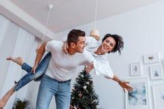 Attraktiv gladlynt man och kvinna som har gyckel nära julträd Helgdagsafton för ` s för nytt år royaltyfri fotografi