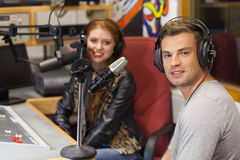 Attraktiv gladlynt radiovärd som intervjuar en gäst Royaltyfri Bild