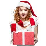 Attraktiv gladlynt ung kvinna i hållande gåva för santa hatt Arkivbild