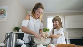 Attraktiv goda som ser modern, och hennes lilla dotter som försöker att göra ren deras händer från en deg, medan laga mat tillsam stock video