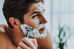 Attraktiv grabb som rakar hans skägg vid rakkniven arkivfoto