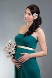 Attraktiv gravid kvinna i grön klänning med blommor som drömmer nolla Arkivbilder