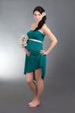 Attraktiv gravid kvinna i grön klänning med blommor som poserar ove royaltyfria foton