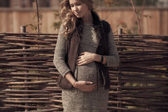 Attraktiv gravid kvinna i slags tvåsittssoffakläder på bygd royaltyfri foto