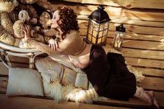 Attraktiv gravid kvinna som ligger på päls med en bok Royaltyfri Foto