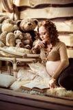 Attraktiv gravid kvinna som ligger på päls och läseboken Royaltyfri Bild