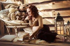 Attraktiv gravid kvinna som ligger på päls och läseboken Royaltyfri Foto