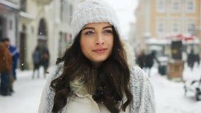 Attraktiv härlig dam som går över snöig stadsbakgrund stock video