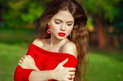 Attraktiv härlig flicka med modeörhänget som bär i röd dr Royaltyfri Fotografi