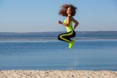 Attraktiv härlig idrottsman nenbanhoppning under sportar på stranden i morgonen Arkivfoton